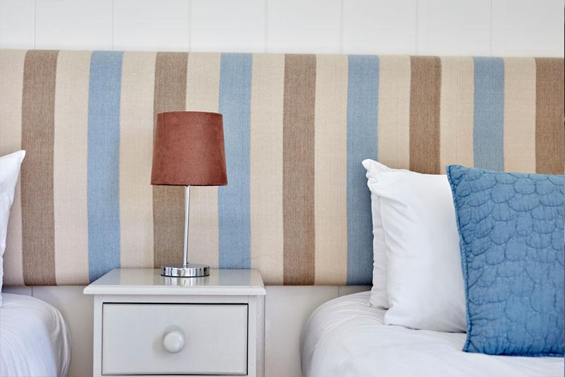 Stripped headboard in twin bedroom of 3-bedroomed lodge
